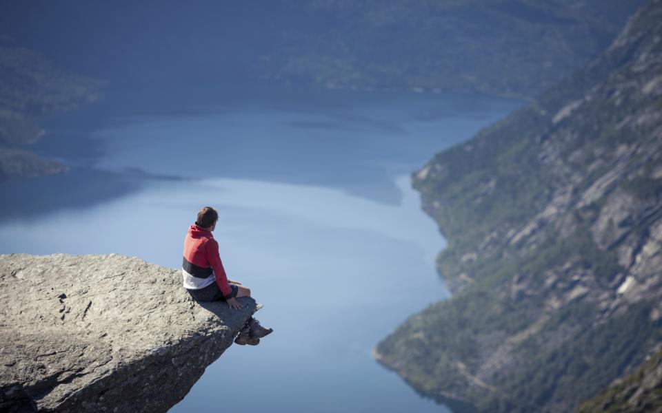 Überblick: Mann sitzt auf Felsvorsprung